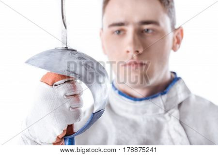 Close-up View Of Young Man Professional Fencer Holding Rapier On White