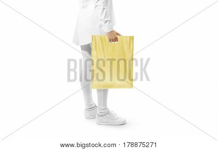 Blank yellow plastic bag mockup holding hand. Woman hold clear carrier sac mock up. Plain bagful branding template. Shopping carry package in persons arm. Promotional packet for logotype branding.