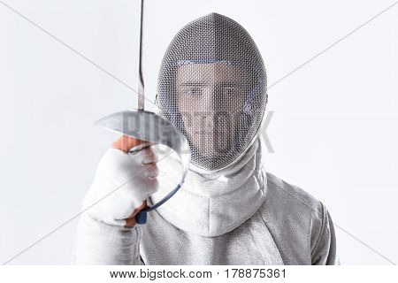 Portrait Of Fencer In Uniform Holding Rapier In Hand On White