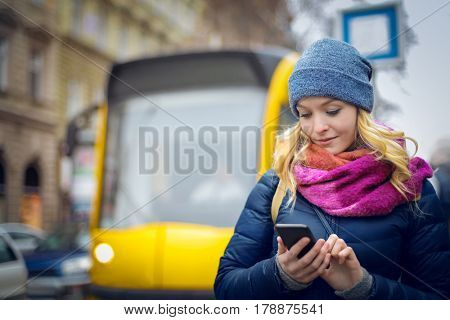 Blonde girl checking her phone while walking in the city