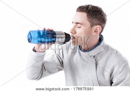 Side View Of Fencer Drinking Water From Bottle On White