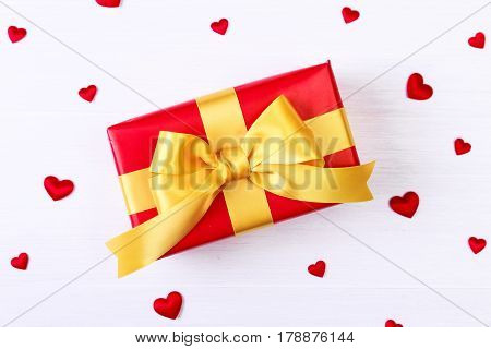 Gift box with red satin hearts. Present wrapped with yellow ribbon. Christmas or birthday package. On white wooden table.