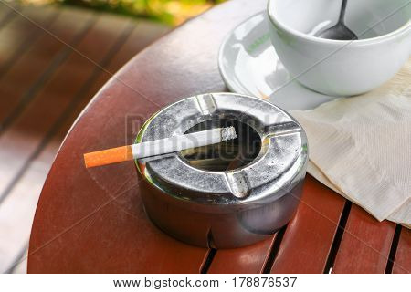 Cigarette in ashtray Placed on table wood background select focus with shallow depth of field.