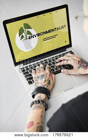 Tattooed hands going green on laptop