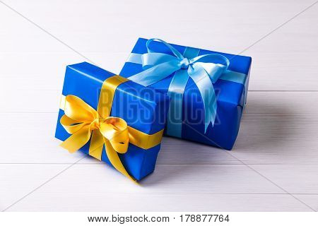 Gift boxes with bow. Presents wrapped with paper and ribbons. Christmas or birthday packages. Celebration design. On white wooden table.