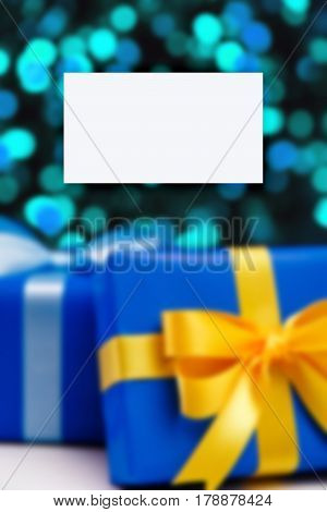 Business card mockup. Gift boxes on blurred background. Colored presents wrapped with paper, bow and ribbons. Christmas or birthday packages.