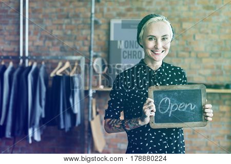 Fashion designer tattooed girl holding open shop banner