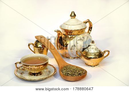 Golden tea set with a spoon full of herbs on white background