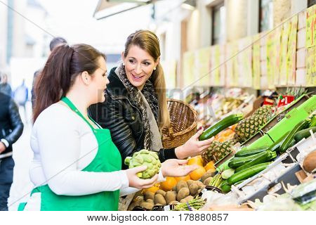 Woman buying groceries at farmers market stand
