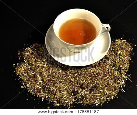 cup of tea and herbs on a wooden Net Worth on a black background