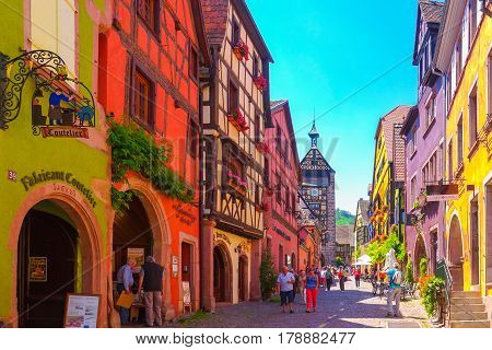 Riquewihr France-June 23 2016: Tourists are walking on the main shopping street; Rue du General de Gaulle in Riquewihr Alsace France