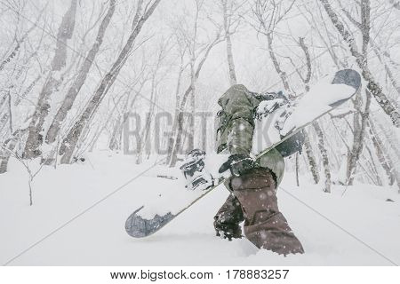 Unrecognizable freerider young man with snowboard walking in winter forest among snowdrifts