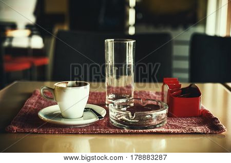 Closeup view on cup of coffee ashtray and empty glass of water.