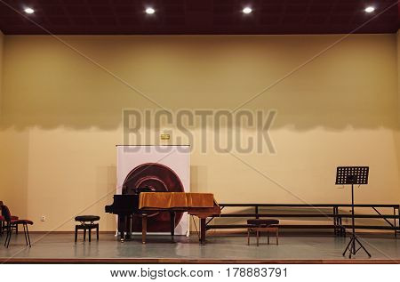 Details of an empty small concert hall with stage piano and some chairs on it.