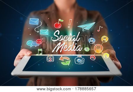 Casual young woman holding tablet with social media icons