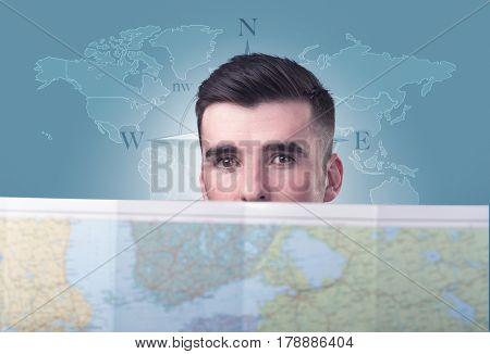 Handsome young man holding a map with a world map and a compass behind him