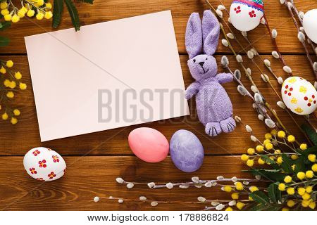 Handmade easter card with painted eggs and bunny on wood background. Colorful holiday decoration on rustic table top view