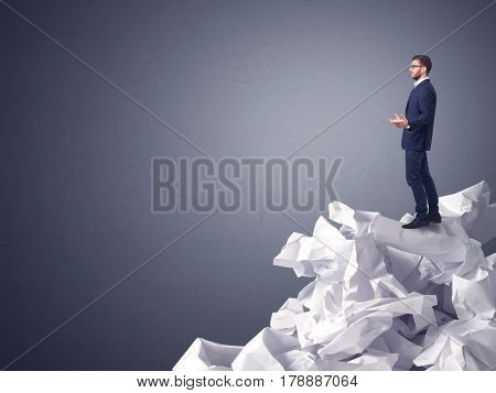 Thoughtful young businessman standing on a pile of crumpled paper with a dark grey background