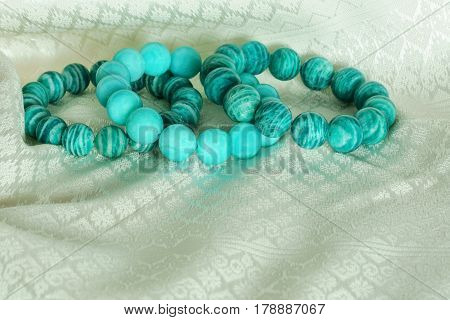 Beautiful Amazonite or Amazon stone beads in bracelets on Thai silk cloth background