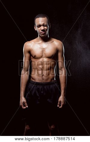 African American Muscular Man Blinking And Posing On Black
