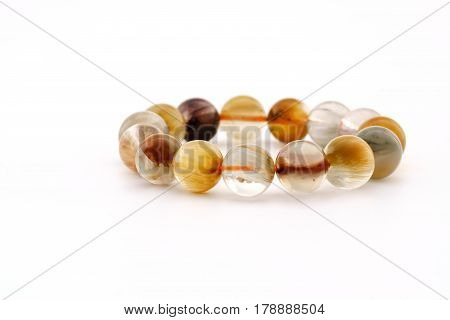 Beautiful translucent assorted colors Rutilated Quartz or Venus' hairstone bead in bracelet on white background