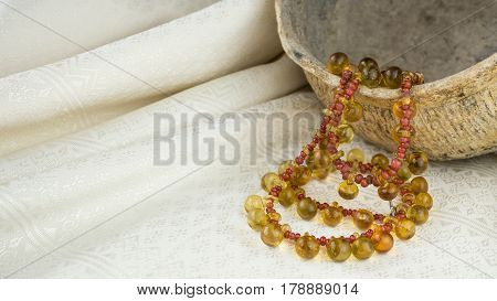 Ancient yellow glass button necklace separated by small red trade beads on a pot and Thai silk background