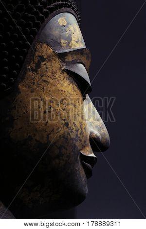 Closeup buddha face statue on black background. Buddha face