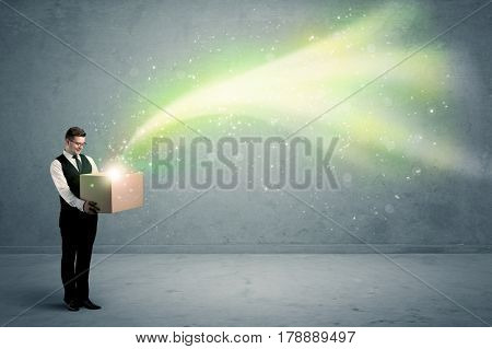 Bright yellow, green light beams escaping a cardboard box held by young elegant male business person in stylish suit concept.