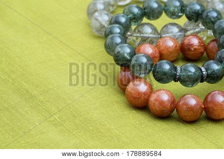 Beautiful translucent assorted colors Rutilated Quartz or Venus' hairstone bead in bracelets on green Thai silk cloth background