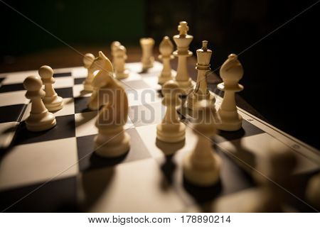Image of the white pieces on a chess board with shallow depth of field.