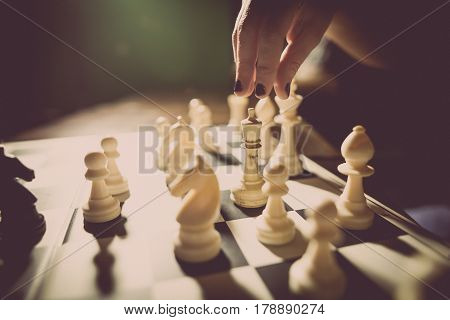 Image of the white pieces on a chess board with shallow depth of field and a hand preparing to move.