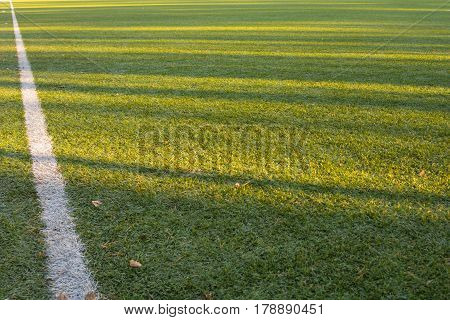 The artificial turf green grass on the football field with the white lines.