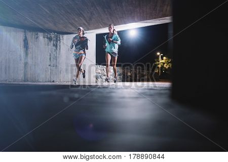 Two young female runners running together at night in city. Young women jogging under bridge at night.