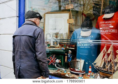LONDON, UK - MARCH 18, 2017: Man looking at the window display of Nauticalia store in Greenwich. The shop located just yards from the Meridian line.