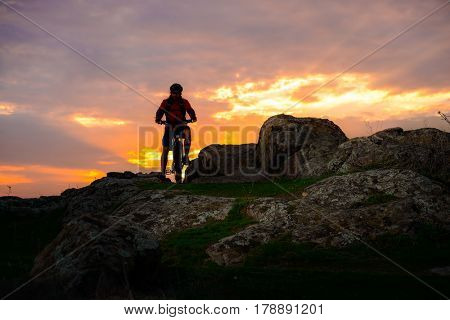 Silhouette of Cyclist with the Mountain Bike on the Spring Rocky Trail at Beautiful Sunset. Extreme Sports and Adventure Concept.