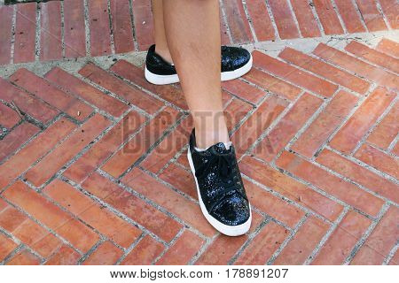 Fashion sneakers glittering style abstract background, people wearing black sneakers