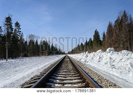 Railroad in snow-covered forest in early spring