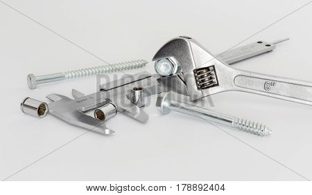 Adjustable wrench calipers heads and screws on white background closeup