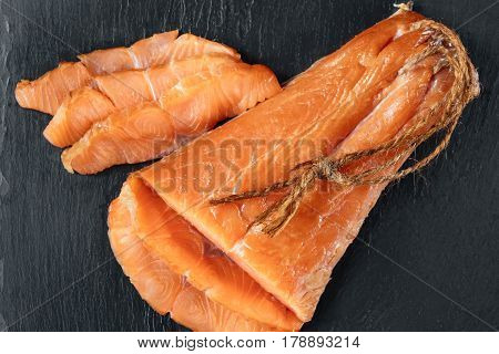 Smoked salmon fish on a slate board. Top view at cutted slices of smoked salmon