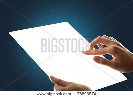 Young female hand holding and touching a piece of glass meant to look like a tablet