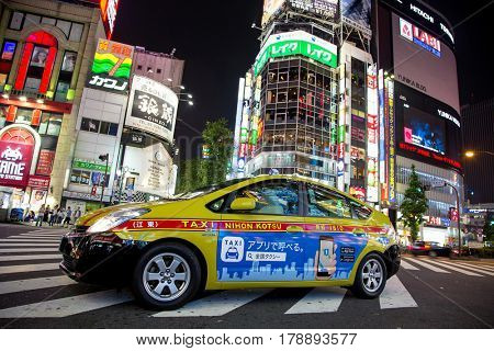 Tokyo, Japan - 19 June 2016: Toyota Prius, energy efficient taxicab in Shinjuku, Tokyo. Night scene  on busy intersection in the commercial shopping district.