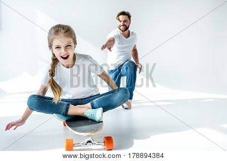 Smiling Father Looking At Happy Daughter Sitting On Skateboard