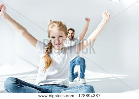 Happy father and daughter cheering with raised hands on grey