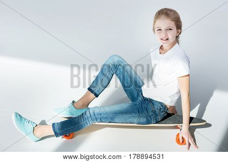 Cute Little Girl Sitting On Skateboard And Looking At Camera