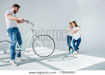 Laughing Mother And Daughter Looking At Emotional Man Having Fun With Bicycle