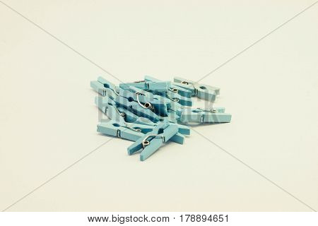 A set of blue wooden clothespins on white background