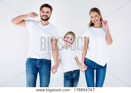 Happy Family In White T-shirts Cleaning Teeth With Toothbrushes On White