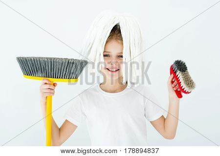 portrait of smiling little girl holding various cleaning supplies on white