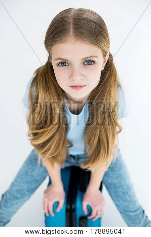 Adorable Girl Sitting On Suitcase And Looking At Camera In Studio On White