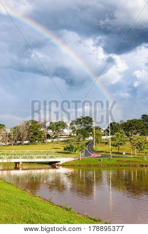 Unny Afternoon At Park After Rain With A Beautiful Rainbow On Background